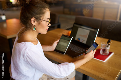Fotomural  Mixed race woman in glasses working with multiple electronic internet devices