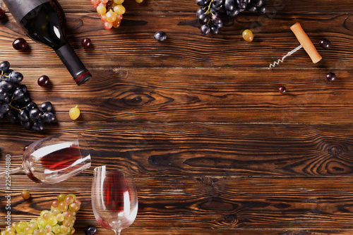 Fotografía  Vintage bottle of red wine with blank matte black label, corkscrew & bunches grapes on wooden table background