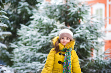 A Little Girl In A Yellow Jacket Plays Snowballs In The Winter, Throws Snow, Runs Along A Snowy Road Amid Snowy Fir Trees And The City