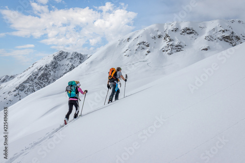 Tela Ski touring couple hiking up a summit in the alps