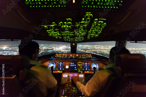 Photo Asian airline pilots were operating commercial aircraft on approach phase over city on the night