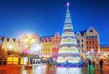 Wroclaw, Poland, Christmas Market Square And Illuminated Christmas Tree In The Center Of Old City. New Year Ambiance, Illuminated And Ornamented Festive City. Night Scene.