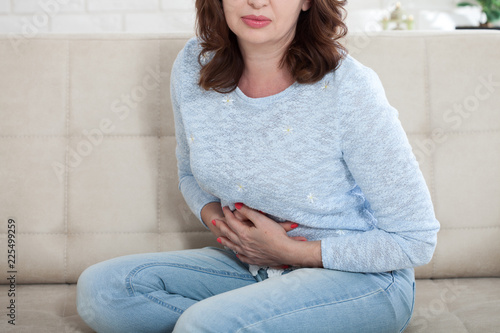 Middle aged woman suffering from abdominal pain while sitting on bed at home Wallpaper Mural