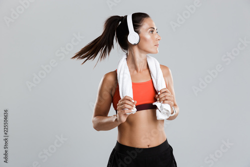 Staande foto Hoogte schaal Strong young sports woman isolated indoors with towel on neck listening music with headphones.