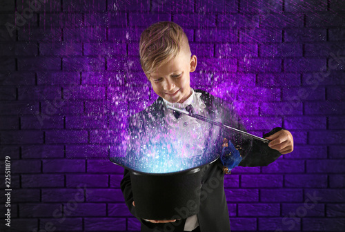 Cute little magician showing trick with hat against dark brick wall Canvas Print