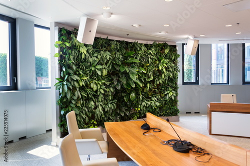 Obraz Living green wall, vertical garden indoors with flowers and plants under artificial lighting in meeting boardroom, modern office building - fototapety do salonu