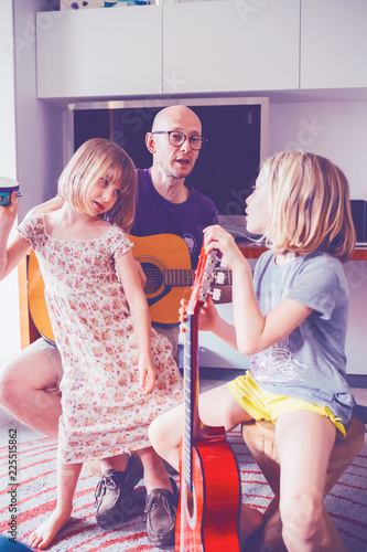 Fotografie, Obraz  father teaching to his two daughter how to play guitar - teaching, learning, hob