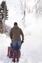 Man Using Snow Blower Machine In Snowy Region