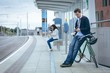 Businessman leaning on bicycle and using smartphone at railway station