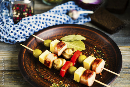 fried sausage with cheese and mushrooms with vegetables on a wooden skewer