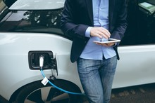 Businessman Using Digital Tablet While Charging Electric Car