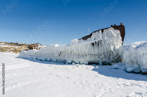 Old iron ship covered with ice at lake in winter