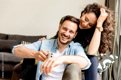 Obraz Young loving couple relaxing in the room - fototapety do salonu