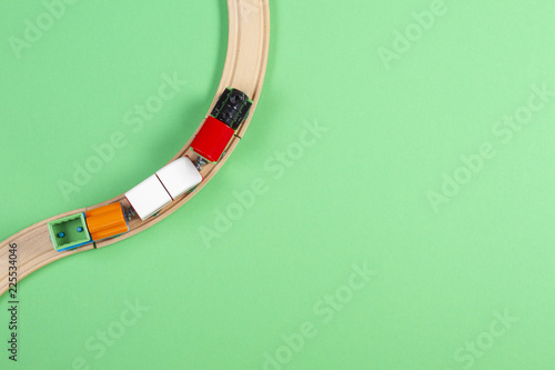 Foto  Toy train and wooden rails on green background