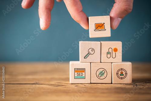 Photo  Hand stapelt Online-Marketing Komponenten als Symbole auf Würfeln