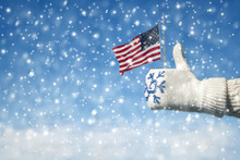 Female Hand In A Knitted Mitten With A Snowflake With An American Flag On The Winter Snowfall Background. Hand Thumb Up And Good Symbol USA Victory And Freedom. Concept.