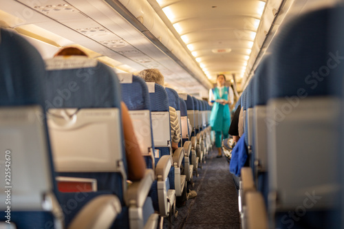 Tuinposter Interior of commercial airplane with passengers on their seats during flight.