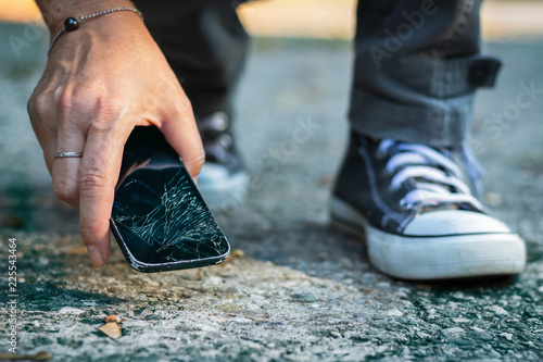Woman picking up broken smartphone from the ground