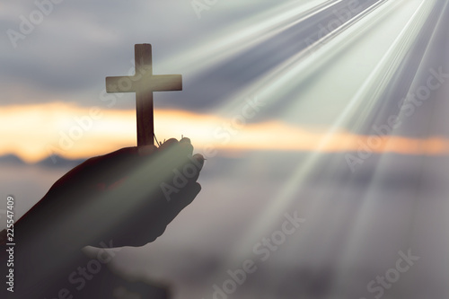 Photo Silhouette of cross in human hand, the background is the sunrise