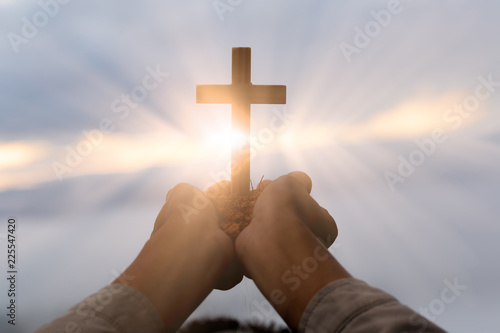 Obraz na plátně Silhouette of cross in human hand, the background is the sunrise