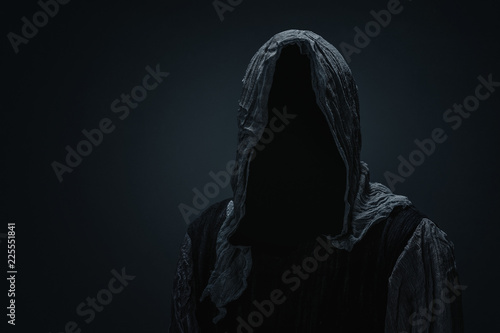 Silhouette of Grim Reaper over dark gray background with copy space