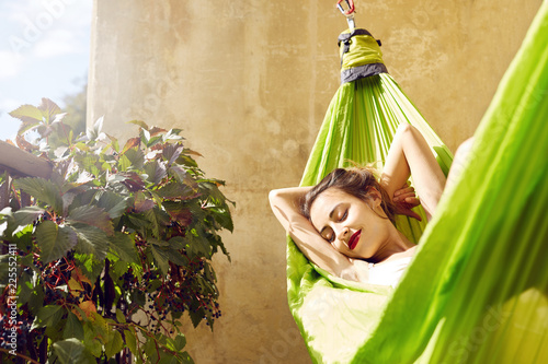 Fototapeta happy young woman relaxed lies in a hammock on the balcony House