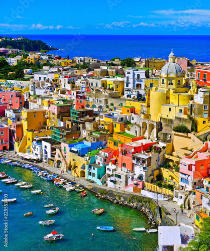 View of the Port of Corricella with lots of colorful houses on a sunny day in Procida Island, Italy. © Javen