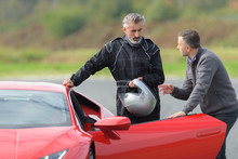 2 Men On A Race Track Talking Near A Ferrari