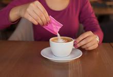 Young Woman Adding Sugar In Coffee