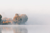 Panorama of calm autumn lake with fog over water and reflections of trees. - 225557083