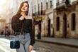 Outdoor portrait of yong beautiful fashionable woman wearing stylish black white polka dot blouse, blue jeans, red earrings, with small quilted bag. Model posing in street of european city. Copy space