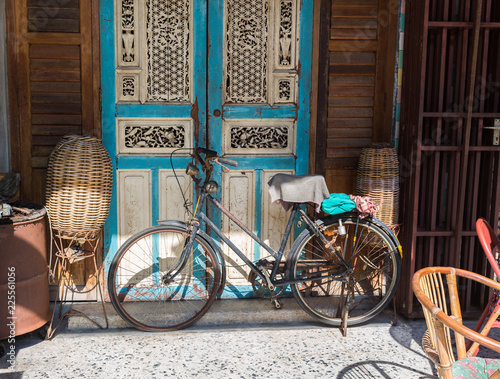Poster Fiets Old bicycle leaning against grungy barn in Thailand