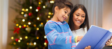 Family, Holidays And People Concept - Happy Mother And Daughter Reading Book Over Christmas Thee Lights Background