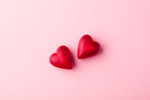 Two Chocolate Heart Candies Pink Pastel Paper Background. Top View. Copy Space.