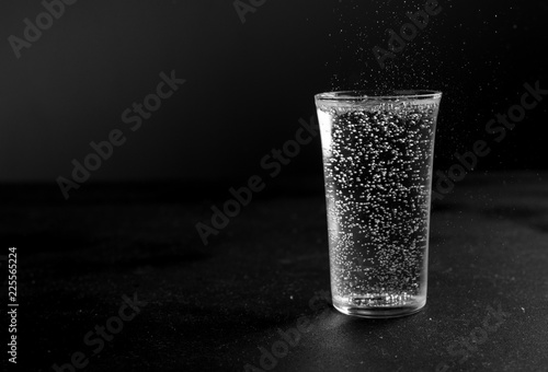 Glass of carbonated drink with ice on a black slate