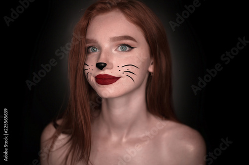 Smiling redhead girl woman with cat carnival halloween makeup posing isolated over black wall background looking at camera Wallpaper Mural