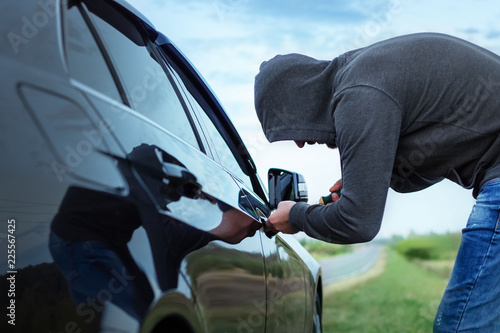 Photo car thief in action, a man in a hood breaks a screwdriver car door