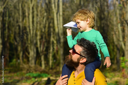 Flying is the perfect vocation for a man who wants to feel like a boy. Little son dream of flying on fathers shoulder. Child boy and father launch paper plane in park