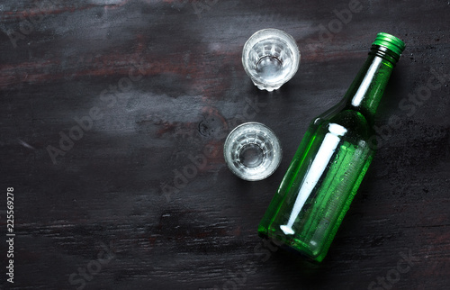 Alcoholic clear distilled korean Soju bottle with shot glass on a wooden background.