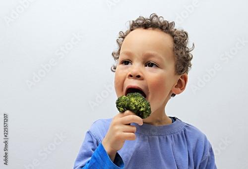 little boy enjoying broccoli stock photo Fototapete
