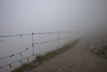 Close-up Of Orange And Yellow Net Fences At The Snowy Ski Slopes Of The  Kasprowy Wierch Peak , Deep Fog In Background. Poland