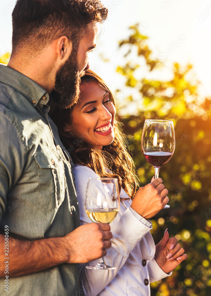 Fototapeta Portrait of young smiling man and woman tasting wine at winery vineyard - Young people enjoying harvest time together. Romantic love.