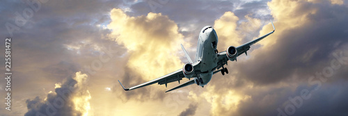 Jet Airliner Flying in a golden coloured cumulus cloudy sunset sky Canvas Print