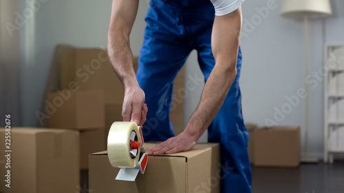 Fotografía  Moving company worker packing cardboard boxes, quality delivery services