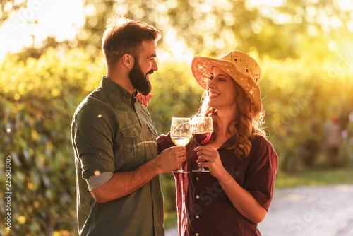 Foto Portrait of young smiling man and woman tasting wine at winery vineyard - Young people enjoying harvest time together