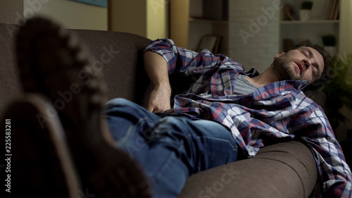 Fotomural Untidy drunkard sleeping on couch after home party, alcoholism consequences