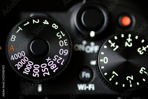 Fotomural  Shutter Speed dial of a digital camera in black background.