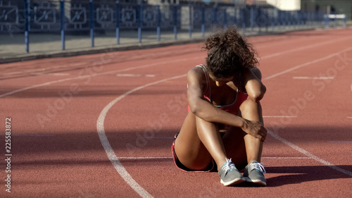 Fotomural Biracial sportswoman exhausted after tough trainings sitting in middle of track