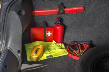 Wnętrze bagażnika samochodu w którym znajduje się apteczka samochodowa, gaśnica, trójkąt ostrzegawczy, kamizelka odblaskowa, kable rozruchowe oraz linka holownicza.