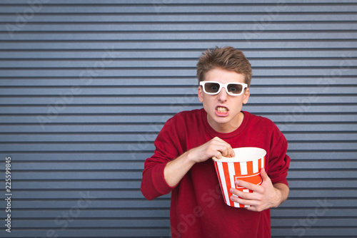 Fotografie, Obraz  Emotional young man in 3d glasses stands on a dark background, eating popcorn and cup with angry eyes looking into the camera